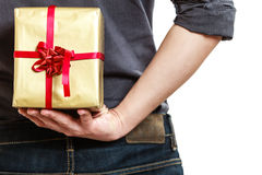Holiday. Man hiding surprise gift box behind back Stock Photography