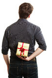 Holiday. Man hiding surprise gift box behind back. Holiday and special occasion. Man giving golden gift box with red ribbon isolated on white. Guy hiding present Royalty Free Stock Photo