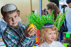 Holiday market in Jerusalem. The Jewish holiday of Sukkot,  Holiday market in Jerusalem. Cute little boy with long blond hair in  knitted skullcap and  seven Royalty Free Stock Photography