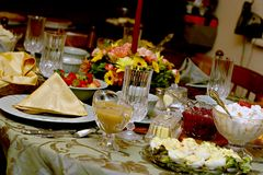 Holiday Meal Table. Close-up view of a table set for a festive meal, with deviled eggs, ambrosia, cranberries and gravy served in crystal, and flowers in Stock Image