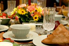 Holiday Meal Table Setting. Close view of a table set for a festive meal, with  flowers in background Stock Images