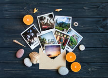 Holiday memories: photos, stones, seashells, fruits on travel photo. Flat lay, top view Stock Photos