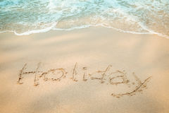 Holiday message hand writing on the sand beach Royalty Free Stock Photo