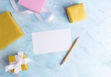 Holiday mockup: top fiew flat lay gold and pastel pink gift boxes with white ribbon, empty card and pencil on blue background. Gre Royalty Free Stock Photography