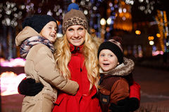 Holiday mom with her kids. Holiday mom with kids in new year on street at night Stock Photography