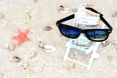 Holiday money concept - Banknotes with sunglasses in a beach chair and sand background royalty free stock photography