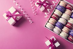 Holiday mood with gift boxes and colored sweet macaroons. On pink background stock photography