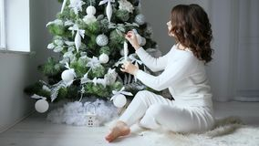 Holiday morning, girl with brown hair decorates festive Christmas tree in soft white tones. Holiday morning, girl with brown hair decorates a festive Christmas stock video footage