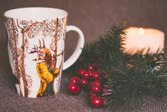 Holiday Mug With Green Holly Branch and Candle Stock Photos