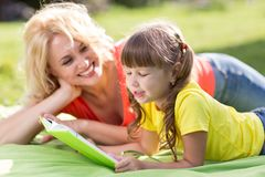 Holiday in nature. Mother and child daughter having fun on the lawn. stock photos