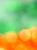 Holiday orange and green background. Orange sparkles on blurred green background Stock Image