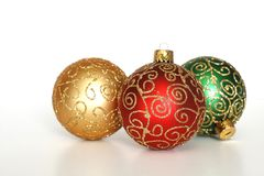Holiday ornaments. Three colorful holiday ornaments, gold red and green Stock Photography