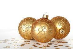 Holiday ornaments. Three colorful holiday gold ornaments with star confetti Stock Photography