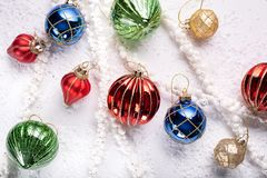 Holiday ornaments on white with snow and beads. Top view royalty free stock photography