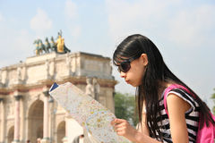 Holiday in Paris. Girl with map in Paris, at the Arc de Triomphe du Caroussel Royalty Free Stock Image