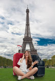 Holiday in Paris. Happy girl on the phone with her baggage by the Eiffel Tower stock photo