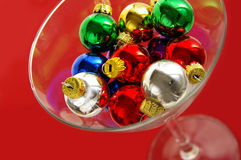 Holiday party. Christmas ornaments in a martini glass on red background holiday party concept royalty free stock images