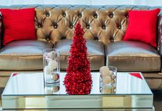 Holiday Party couch and coffee table in red and white themed decor. Holiday Party in red and white themed decor with glitzy mirror decor accents Stock Photo
