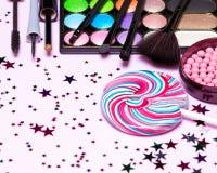 Holiday party makeup cosmetics with lollipop and confetti. Holiday party makeup cosmetics. Color glitter eyeshadow, blush, liquid eyeliner, mascara, brushes with Stock Photos