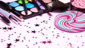 Holiday party makeup cosmetics with lollipop and confetti. Holiday party makeup cosmetics. Color glitter eyeshadow, blush, liquid eyeliner, mascara, brushes with Stock Image