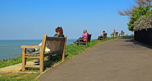 Holiday people on benches Royalty Free Stock Photos