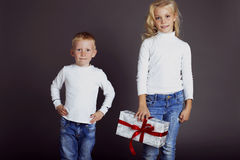 Holiday photo with the little boy and girl dressed in jeans and a white sweater happy and keep Christmas gift Stock Photography