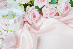 Holiday pink composition. Pink roses, round gift box and a pearl necklace on a silk fabric, holiday pink composition with copy-space royalty free stock images