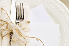 Holiday place setting. With napkin, fork and knife tied with a gold ribbon. Blank card included for your text royalty free stock photography