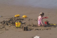 Holiday play. Small girl making sand castle on beach with bucket and spade stock photo