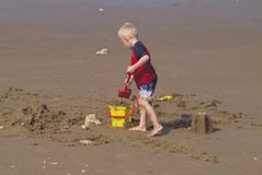 Holiday play. Small boy making sand castle on beach with bucket and spade stock image