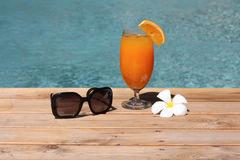 Holiday pool side. Cocktail, sunglass,  flower and swimming pool holiday started Royalty Free Stock Photography