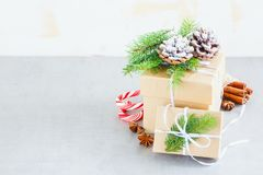 Holiday Cristmas Card. Holiday present boxes wrapped in kraft paper, Fir Branches and Festive Decoration on White Background.  Christmas Greeting Card with space Stock Image