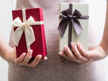 Holiday present surprise woman hold gift box. Holiday present surprise. woman holding two gift boxes behind her back. male and female package colors Stock Image