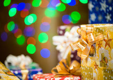 Holiday presents at abstract background. Colorful gift boxes with ribbons at abstract colorful lights background Royalty Free Stock Images