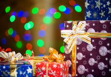 Holiday presents at abstract background. Colorful gift boxes with ribbons at abstract colorful lights background Royalty Free Stock Photos