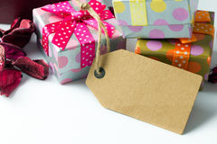 Holiday presents with empty tag. Close up of gift boxes with empty label tag Royalty Free Stock Photo