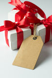 Holiday presents with empty tag. Close up of three gift boxes with empty label tag Stock Photos