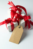 Holiday presents with empty tag. Close up of three gift boxes with empty label tag Royalty Free Stock Photography