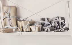 Holiday presents, gift boxes on white shelves at wall background Royalty Free Stock Photos