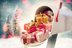 Holiday presents in the mailbox. Holiday presents in the open full mailbox with Christmas decorations background. Concept of sending gifts by mail in holiday stock photos