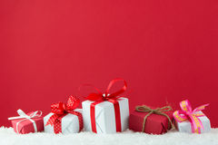 Holiday presents. With ribbon in a row on snow with red color background Royalty Free Stock Photos