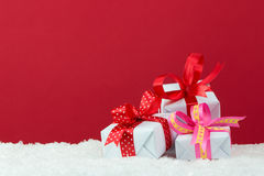 Holiday presents. With ribbon on snow with red color background Stock Photos