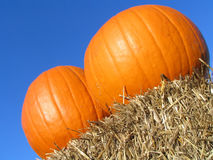 Holiday Pumpkins. Two Pumkins Sitting on a Hay Bale Stock Photography