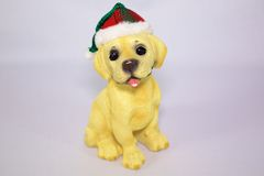 Holiday Puppy Statue. A statue of a puppy wearing a holiday hat against a white background Royalty Free Stock Photography