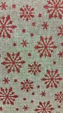 Holiday Red Glitter snowflakes on natural burlap texture. Red glitter snowflakes holiday design on natural burlap textured background Royalty Free Stock Image