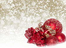 Holiday Red and Gold Decorations On A Snowy Backgr. Red holiday ornaments and gold accents on illustrated snowy champagne bokeh background Royalty Free Stock Photography
