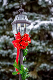 Holiday Red Ribbon on a yard light.  Stock Photos