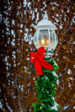 Holiday Red Ribbon on Yard Light. Christmas decoration on streetpost Royalty Free Stock Images