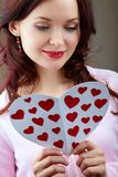 Holiday regards. Portrait of young woman holding Valentine card and reading it Stock Photo