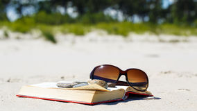 Holiday relax. The book and sunglasses on the beach Royalty Free Stock Image